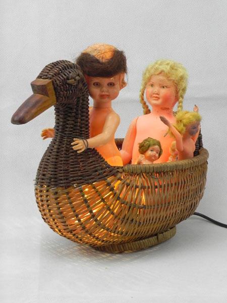 Contard.Composition lumineuse d'objets. Assemblage panier en forme de canard et 5 poupées de collection.