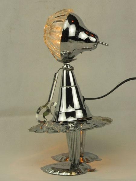 Vegetelle. Petite fille lumineuse en métal chromé. Assemblage d'une coupe de sport, un couvercle en forme de poire, un ramequin en verre...