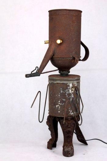 Sculpture assemblage d'objets en métal rouillé, tôle et fonte. Composition: arrosoir, boite, pied en fonte, chausse pied. Upcycling, récup