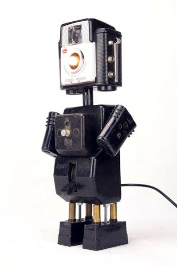 """Robot appareil photo et interrupteur en bakélite. Assemblage de Bakélite, plastique et métal. Le disjoncteur """"Marche, Arrêt"""" garde sa fonction d'interrupteur. Noir et alu. Détournement d'objets vintage plus aux normes."""