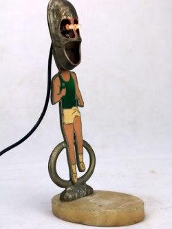 """Sculpture lumineuse sport. Assemblage d'un trophée sportif, """"course"""", petite chaussure en fonte, plaque en marbre. Détournement d'objets."""