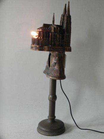Sculpture personnage avec objets souvenirs boite à musique en forme de cathédrale et horloge forêt souvenir sur un bougeoir. Crèche miniature dissimulée.