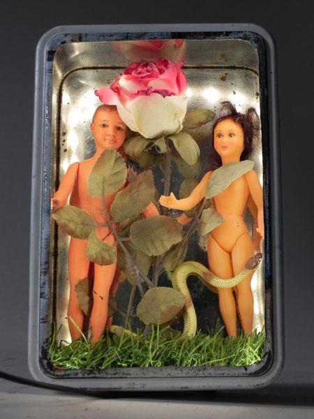 Composition Adam et Eve dans une boite à sucre bretonne. Assemblage: boite en métal, fleur en tissus et 2 poupées en plastique, gazon synthétique .