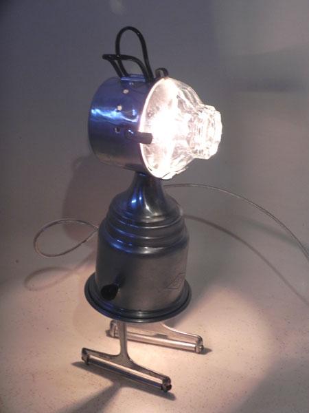 Personnage lumineux en aluminium. Assemblage d'un filtre à café, un bol, une tasse de camping et 2 tranchoirs à fromage.