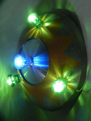 Macaron fête foraine, cône peint en jaune, ampoules de fête foraine vertes et bleues.