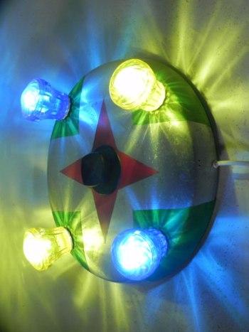 Fête foraine applique lumineuse en aluminium. Couvercle de gamelle peinte en rouge et vert, ampoules de fête foraine bleues et jaunes.