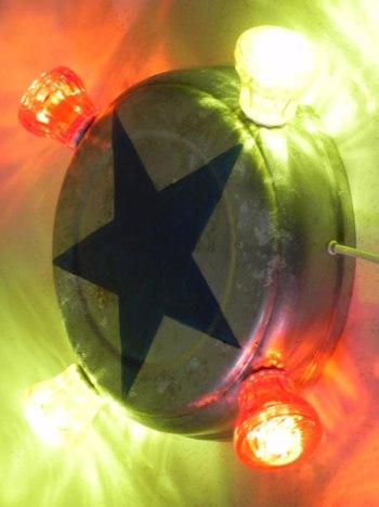 Applique fête foraine, étoile bleu peinte sur une gamelle en aluminium, ampoules de fête foraine rouges et jaunes.