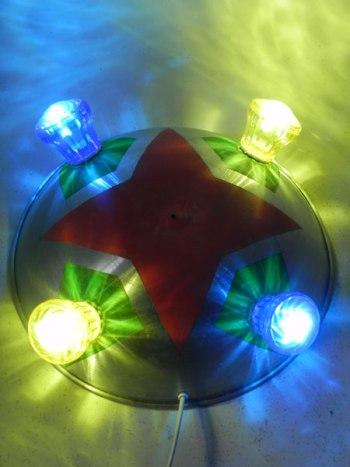 Applique en aluminium et ampoules de fête foraine. Couvercle bombé peint en rouge et vert, ampoules jaunes et bleues.