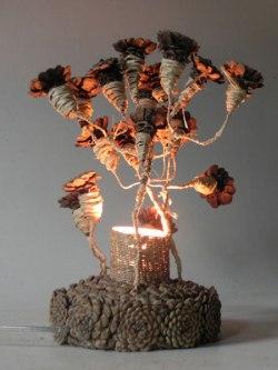 Couronne de fleur en pommes de pin recomposées. Avec ciment, osier, raphia, métal. Ecoconception, recyclage matière locale.