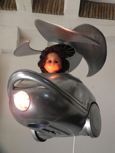 Détournement d'aspirateur en hélicoptère. Assemblage, recyclage lumineux, composé d'un aspirateur cassé, une hélice et une poupée.