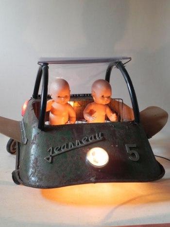 Véhicule volant sculpture lumineuse. Assemblage d'une brouette trouée et retournée,4 roulettes, optique auto moto, 2 baigneurs....
