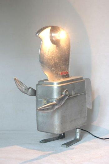 """Sculpture homme oiseau aluminium assemblage d'éléments de trancheuse familiale en fonte d'aluminium, une boite gamelle """"MA.MOU.Marseille 1939"""", pince en forme de crabe et 2 clenches aux pieds."""