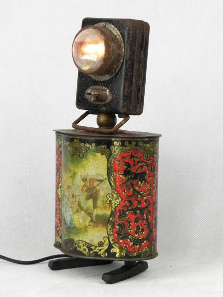 Assemblage lumineux lampe de poche et boite en métal imprimée ancienne, pied en frein de vélo.
