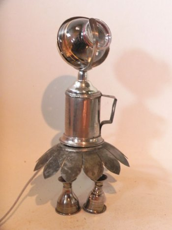 Lampe pigeon détournée, assemblée à une assiette de présentation, petits verres en métal et une coupe en verre.