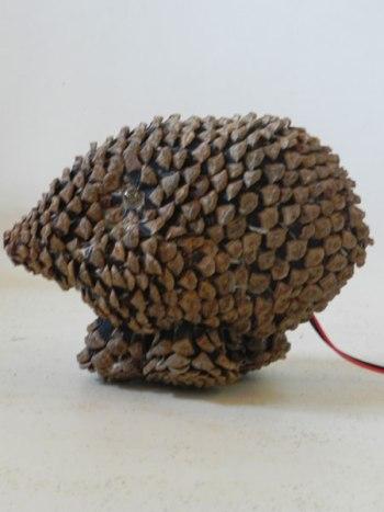 Sculpture animal improbable en pommes de pin démontées et recomposées. Lampe.