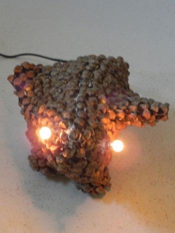 Sculpture animal préhistorique en pomme de pin. démontées et recomposées comme des écailles. Animal improbable lumineux.