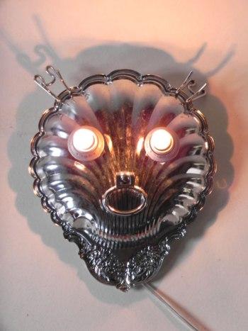 Trophée lumineux tête de lion avec un plat de présentation en forme de coquille, une poignée et deux crochets. Lampe applique.