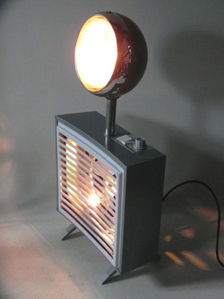 Radiateur et phare lumineux, détournement d'objets. Assemblage d'un chauffage d'appoint soufflant vintage et un phare de voiture.