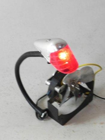 Ancien feu arrière de vélo assemblé à un moteur avec hélice. Assemblage lumineux.