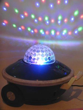 Soucoupe lumineuse aspirateur bleu sur roulettes, jeux de lumière intégré.