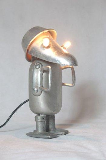 Bonhomme lumineux en aluminium détourné. Assemblage d'un embauchoir, un flacon, un moule, deux poignées de fenêtre et deux anses.