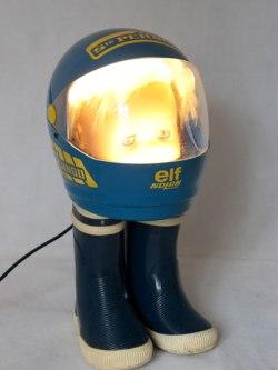 """Baigneur casqué sur bottes. Assemblage: bac à glaçons en forme de casque """"ELF Nolan, écurie Sté Pernod"""", bottes d'enfant, tête de baigneur ."""