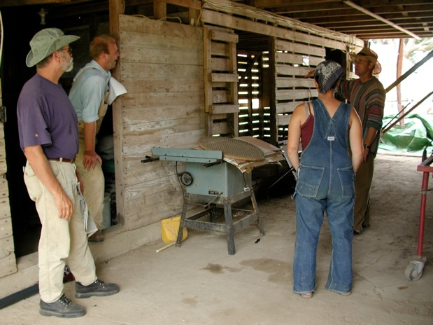 2003, Downstairs of Corn Crib, Center Aisle (Note empty grain bin at near left; wooden ladder to upstairs corn & grain storage; Farmer John at far right.)