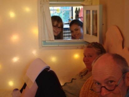 Tom and Nancy Melvin, Lazure painters in foreground in Feather Room. Farmer John's wife Haidy (right) and Finnish friend Milla look in through a tiny window from the barn kitchen. (Window was placed there to serve breakfast in bed to Feather Room guests.)