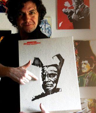 Robert zeigt stolz auf die Angelika Box, im Hintergrund die Songbilder zum Album