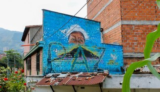 """""""Orion never again"""" reads a mural commemorating 14 years since Operation Orion laid seige to the neighborhood of Comuna 13 in Medellín, Colombia's second largest city. The eyes of human rights activist Luz Elena Galeano Laverde look on as peace grows and origami doves flutter."""