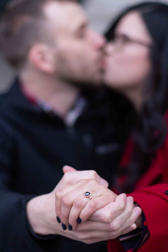 Engagement ring on hand, couple kissing in background.