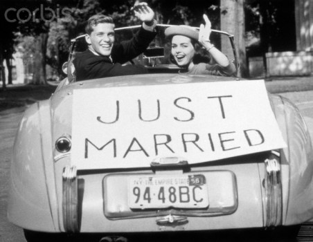 1950s newlywed young couple man woman in convertible sports car with just married sign waving looking at camera da/from www.corbis.