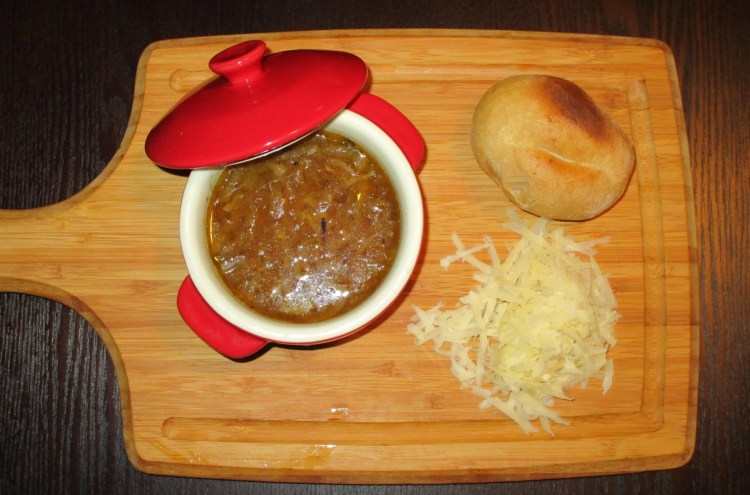 close up serving vegetarian onion soup on board