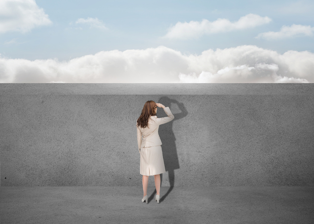 Businesswoman watching a grey wall with the sky in background