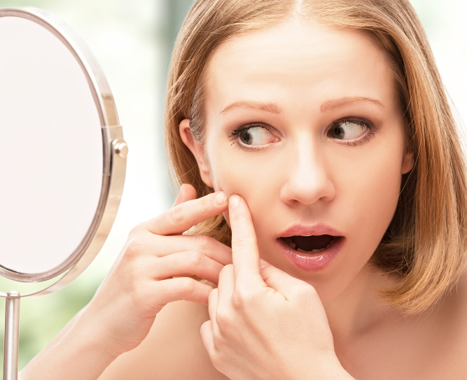 beautiful healthy woman  frightened saw in the mirror acne and w