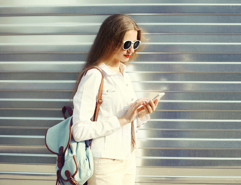 Fashion pretty young woman using smartphone in city over urban g