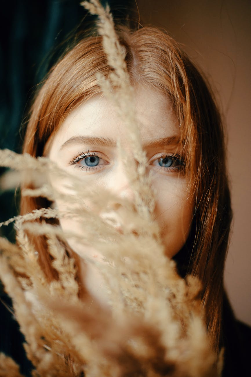 selective focus photography of woman hiding behind flowers