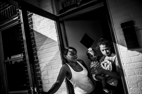 Candy Thomas, 33, with her daughters Zora, 12, and Daria, 8 months, on her porch in the Park Heights neighborhood by the Pimlico race course in Baltimore, Md. on May 7, 2015. Zora fears the police after the death of Freddie Gray, who she knew personally.