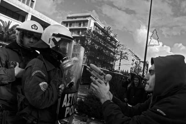 15/12/2008 Athens, after student Alex Grigoropoulos was murdered by a policeman in Exarhia, a massive youngster's insurgerncy took place over one month all over Greece. This became the starting poind of the clashes between the police and the young people while the greek economy was facing the second year of recession, which reached its peak the following years, when the two memorantums were voted by the greek goverments and the enforcement of the austerity measures. The photo is picturing a young student, in a symbolic action, aiming a policeman with a water gun in a midle of a riot.