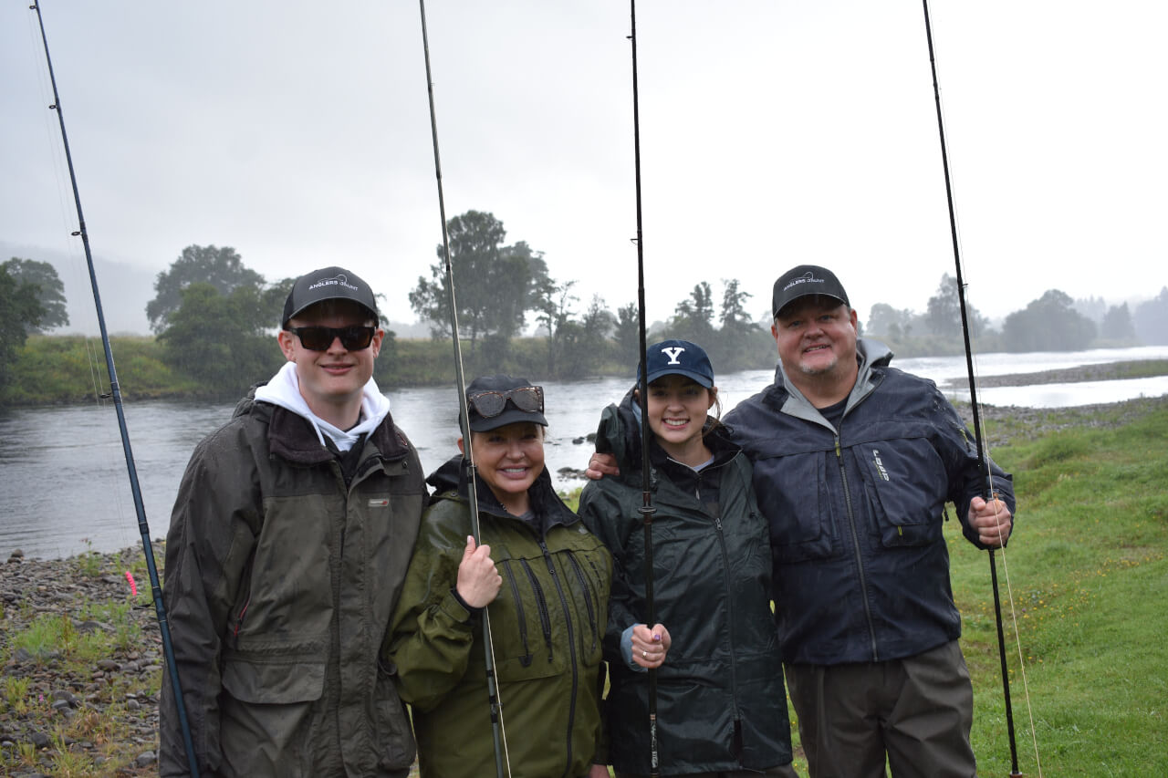 family holding fishing rods beside river during guided salmon fishing trip