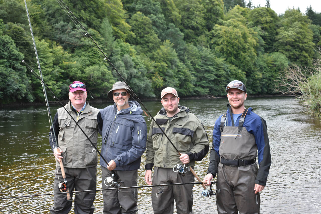 group of anglers standing together on the banks of the river tay during guided salmon fishing trip