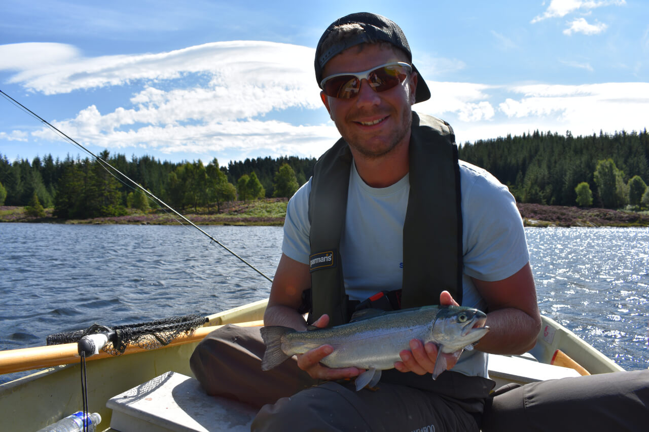 holding a nice rainbow trout caught during guided scottish fishing trip