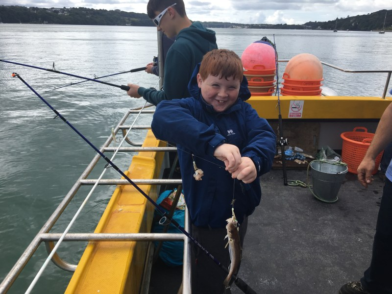 The picture shows a young boy while out on a Starida fishing trip, he has caught a small fish and is smiling