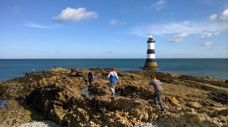 The image show children climbing over the rocks at Penmon Point heading towards the lighthouse