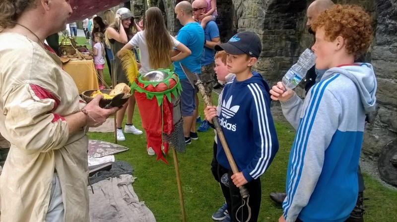 children gathered around a medieval enactment tent, they are being shown weapons of the era, at Beaumaris Castle