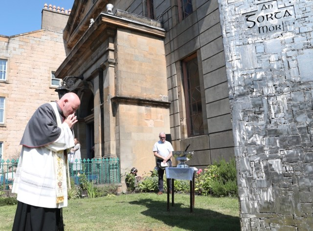 Canon Tom White bows his head in prayer by the side of the memorial, preparing to give the blessing