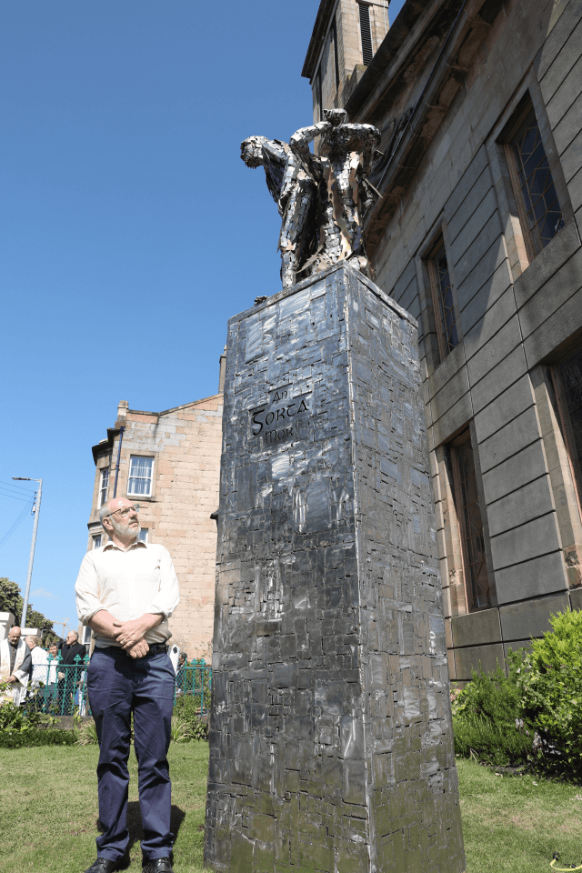"""Sculptor John McCarron with his piece 'The Tower of Silence'. The monument is made of patchwork steel with the words """"an gorta mor"""" on the front of a tall column. On top of the column, gaunt abstract figures represent the starving victims"""