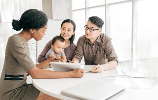 Young family reviewing paperwork with woman