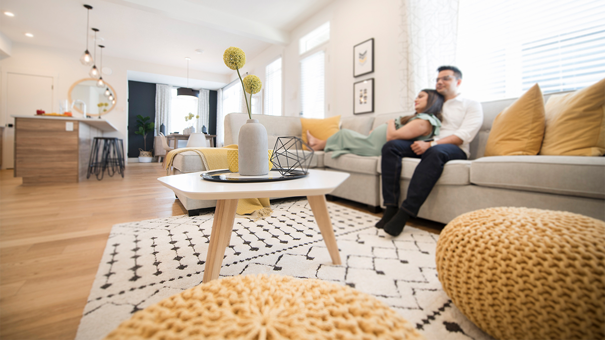 Couple sits in bright living room, featuring mustard yellow accents