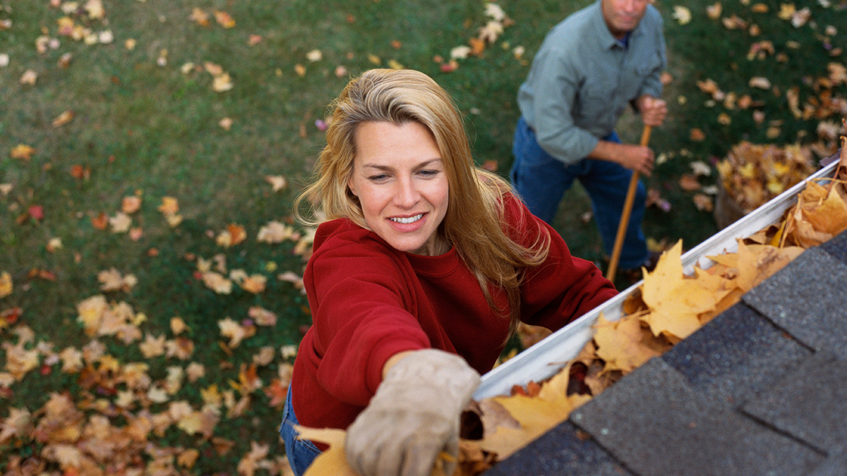 Woman cleaning out the eavestroughs on a home